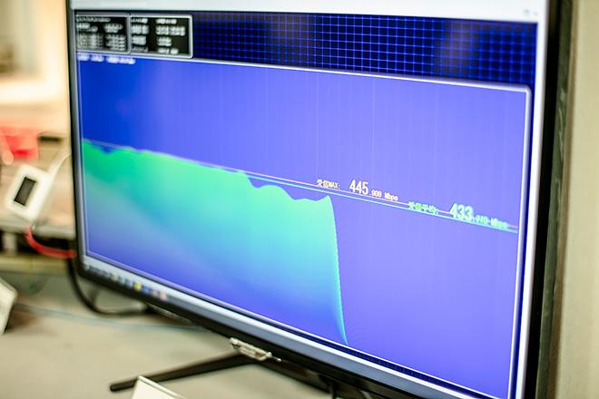 (場所は日立国際電気の5G協創ラボ。ディスプレイに下り445Mbpsが表示されているのがわかる)